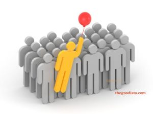 Uniquely able often means being different or standing out from the group illustrated by yellow man holding ballon in a group of grey men.
